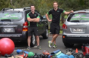 Two Personal Trainers standing infront of cars with exercise equipment